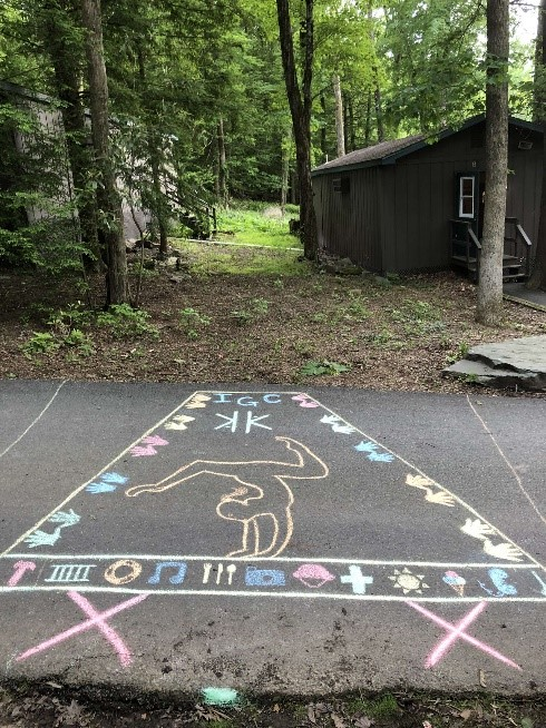 Chalk drawings on pavement. Near is a cabin in the woods.