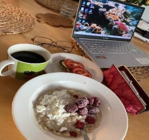 A table with an open laptop, pencil case, a plate with a sandwich on it, a bowl with oatmeal and a mug of dark liquid.