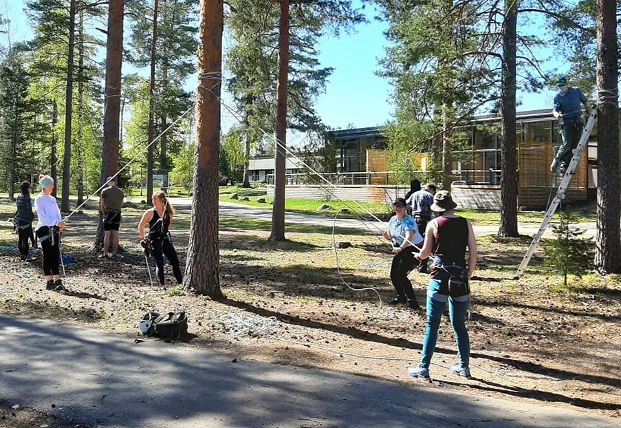 A group of students learning how to use climbing gear by tying ropes on trees.