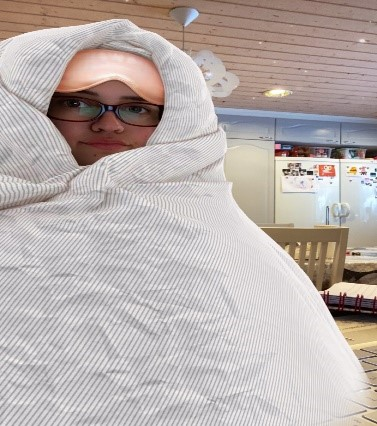 A person wearing glasses wrapped in a blanket with a sleep mask on their forehead.