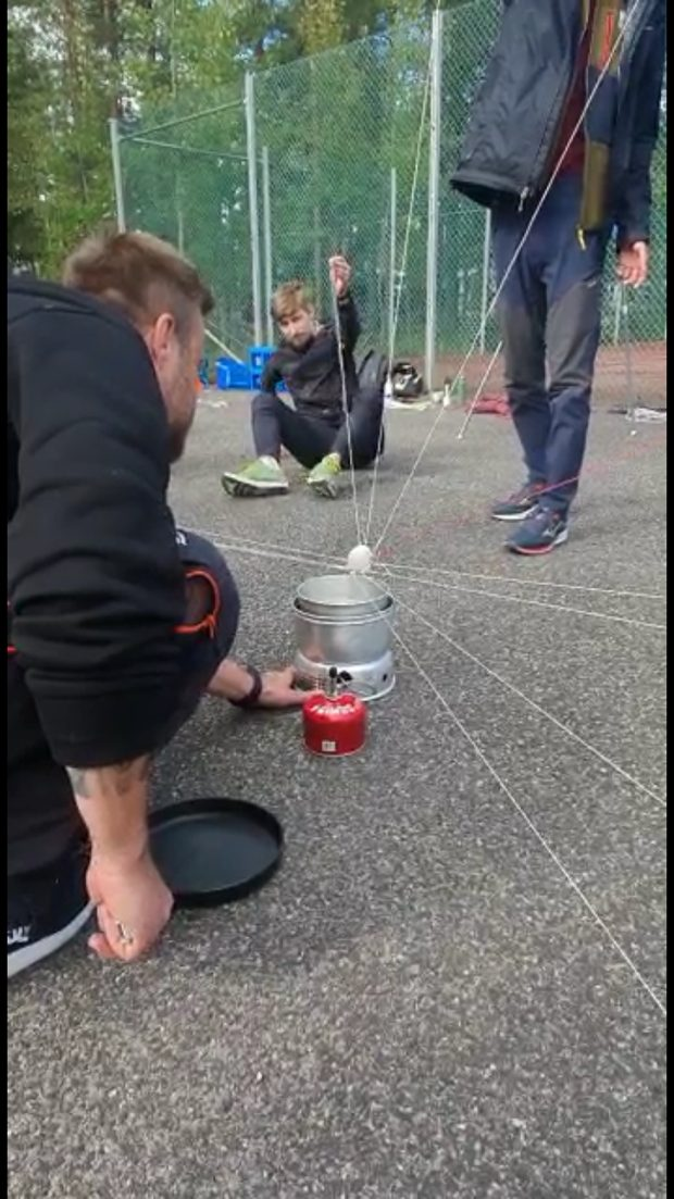 Two students of many holding strings connecting to an egg, which they are collectively trying to boil. One student operates the machine boiling the water.
