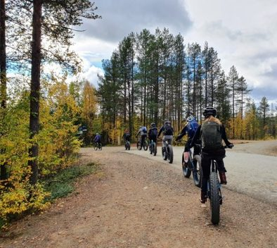 A group of students riding through a forest road on fatbikes.