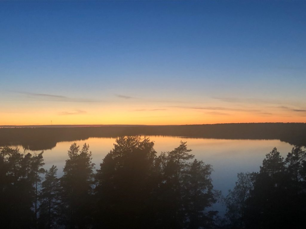 An early morning sunrise over a lake surrounded by trees.